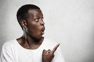 Advertising concept. Midsection of young dark-skinned customer dressed casually, pointing his index finger at blank copy space wall, looking surprised with big sale, opening his mouth widely
