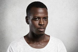 Portrait of confident and handsome young African man dressed casually looking at camera with serious or angry face expression. Dark-skinned model in white T-shirt with scooped neck posing indoors