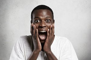 African employee or customer with shocked and surprised face, looking and screaming at camera with big eyes and mouth wide open, holding hands on his cheeks. Human face expressions and emotions
