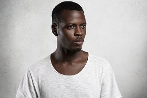Isolated shot of stylish dark-skinned student looking tired and sad, dressed in blank T-shirt, spending free time indoors after lessons at university. Serious African male model posing in studio