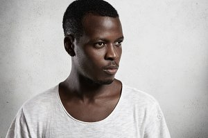 Side view portrait of pensive African man wearing white T-shirt with low neckline looking ahead of him with serious and confident expression, posing isolated against white concrete wall background