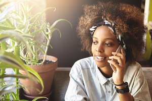 Indoor shot of happy young dark-skinned woman using mobile phone while talking to friends, sitting at window at home. Thoughtful African girl in stylish clothes having nice conversation using gadget