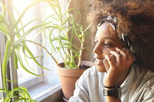 People, technology and communication concept. Cute fashionable dark-skinned woman with Afro hairctyle wearing white t-shirt, having phone talk with her friend and making appointment using mobile