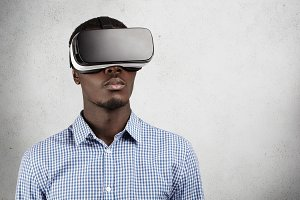 Technology, science, innovation and cyberspace concept. Dark-skinned gamer in checkered shirt, watching something in 3d headset, looking calm and serious. African employee wearing goggles in office