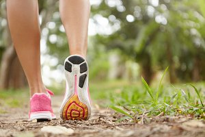 Outdoor activity and sports. Freeze action closeup of pink running shoes against green grass background. Woman jogger exercising in park or forest, getting prepared for marathon. Focus on right sole