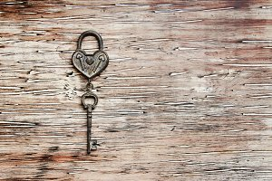 ron key from the lock lying on wooden vintage background