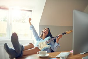 Gorgeous woman with guitar shouting with joy