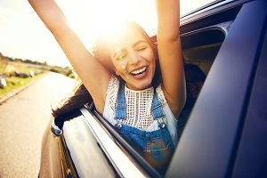 Woman leans out car window and waves her arms