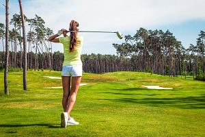 Woman hits the ball on the golf