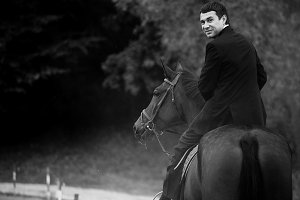 Man in black suit rides a horse