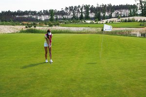 Golfer putting ball in hole #5