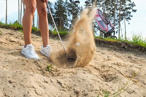 Golfer putting ball from sand