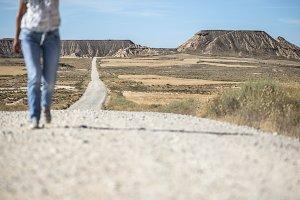 Woman walking on dirt road.