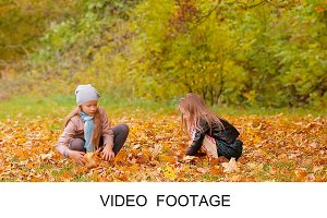 Adorable girls with leaves warm day