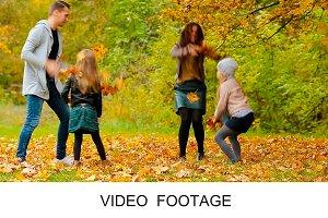 Smiling family enjoy throwing leaves