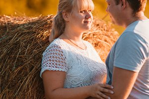 love story man and woman on the background of haystacks  sun