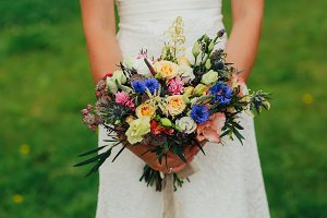 bride holding a bouquet of fresh wildflowers