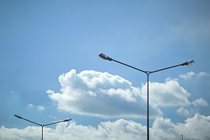 Street light with halogen lamp under cloudy blue sky