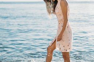 Happy woman walking on pebble beach