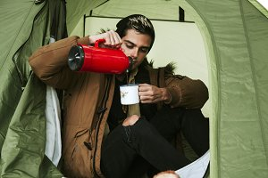 drinking coffee in camping tent in autumn