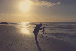 Photographer with Camera on a Beach