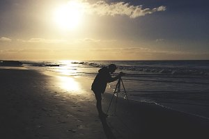 Photographer with Camera on a Beach