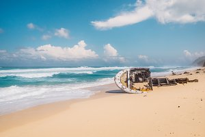 Beautiful secret tropical sea beach with gorgeous waves and old broken boat in Bali island. Exotic outdoor landscape of Indonesia.
