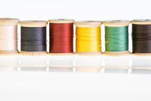 Row of thread spools with reflection