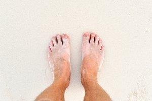 Men legs on sand