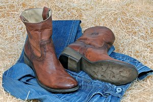Cowboy boots and blue jeans on straw