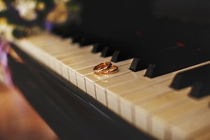 Wedding rings lie on the piano keys