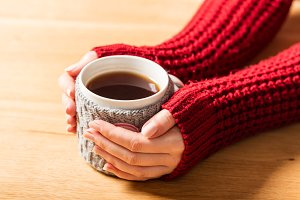 Hot mug of tea warming woman's hands in retro jumper.