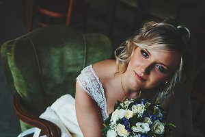 An attractive bride sits in chair
