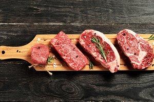 Raw beef steaks on wooden board