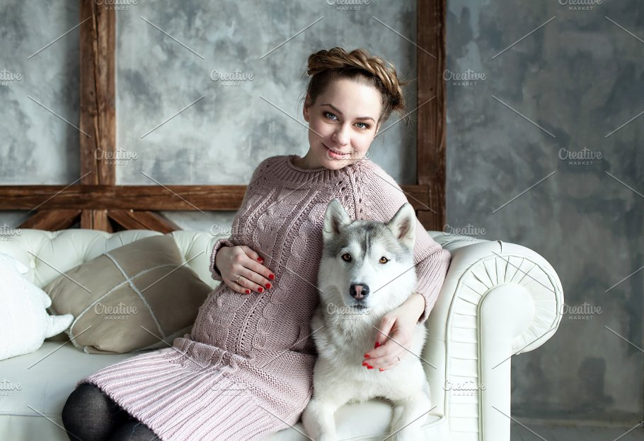 Young beautiful pregnant woman with husky containing woman