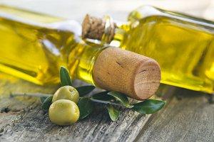 bottles of olive oil and olives on vintage table
