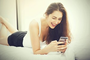 Beautiful Caucasian woman laying down on white bed using mobile phone and smile (Vintage tone)