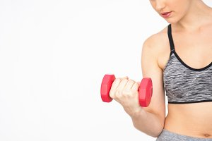Closeup of Young woman lifting dumbbells with copy space over white background - Health and Fitness concept