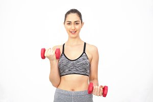 Young Caucasian woman lifting dumbbells over white background - Health and Fitness concept