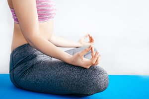 Closeup of woman doing yoga meditation in lotus pose position with copy space