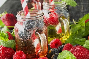 berry juice in a glass with berries, ice and mint