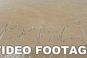 Sea wave washing Brazil written