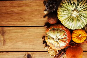 Seasonal wooden table setting with small pumpkins