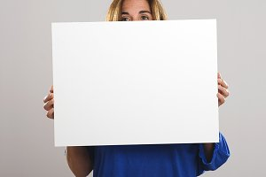 Woman hiding behind a white poster