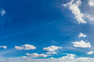 Blue sunny sky with fluffy clouds. Huge panorama