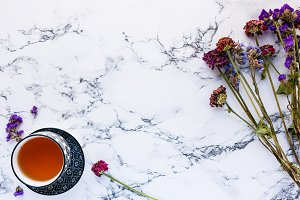 Tea and flowers on white marble