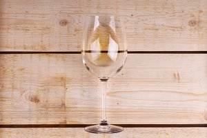 Glass of white wine on wood