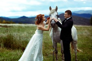 Bride and groom stroke a white horse