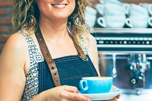 Smiling female barista with coffee