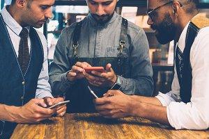 Men using mobile phones at cafe